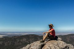 young man sitting on cliff at the Boroka Lookout, Grampians National Park, Australia royalty free stock photo