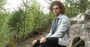 Young man sitting on cliff in forest stock footage