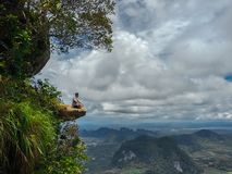 Young man sitting on the cliff with magnificent Mountain View stock images