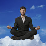 Young man sitting on cloud meditating royalty free stock image