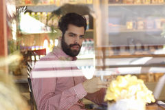Young man sitting in coffee shop Royalty Free Stock Image