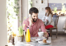 Young man sitting in coffee shop while using his smartphone. Stock Photos