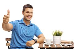Young man sitting at a coffee table and making a thumb up gestur Royalty Free Stock Photography