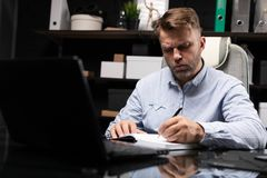 Young man sitting at computer table and makes notes in diary. Busy man works in stylish office with laptop and writes in notebook. Portrait of businessman at stock photo