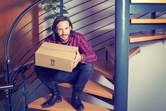 Man sitting in corridor and opening a package stock image