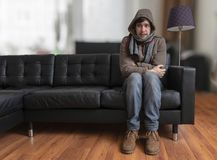 Young man sitting on couch is feeling cold at home. royalty free stock photo