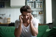 Young man sitting on couch at home have a headache royalty free stock photos