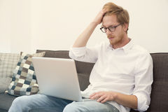 Young man sitting on couch with laptop Royalty Free Stock Photos