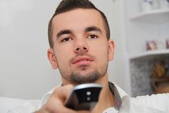 Young man sitting on the couch watching a football game on tv Stock Images