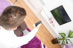 Young man sitting on the couch watching a football game on tv Stock Photography