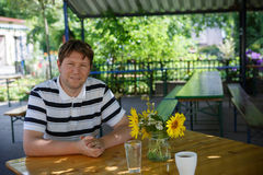 Young man sitting in country cafe and drinking coffee and water Royalty Free Stock Images