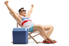 Young man sitting in a deck chair gesturing happiness Stock Images