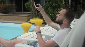 Young man is sitting in deckchair near the swimming pool and typing messeges on his smartphone. stock video