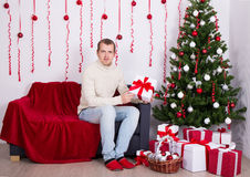Young man sitting in decorated living room Stock Photography