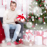 Young man sitting in decorated living room with Christmas tree Royalty Free Stock Photography