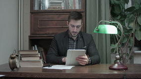 Young man sitting at desk with books using digital tablet in home room office stock video footage
