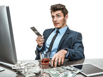 Young man sitting at desk in office and planning how to invest money for profit Stock Photo