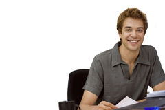 Young man sitting at desk, smiling, portrait, cut out. Young businessman sitting at desk, smiling, portrait, cut out Stock Image