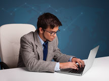 Young man sitting at desk and typing on laptop Stock Photo