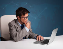 Young man sitting at desk and typing on laptop Royalty Free Stock Photography