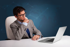 Young man sitting at desk and typing on laptop Stock Image