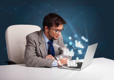 Young man sitting at desk and typing on laptop with diagrams and Stock Photos