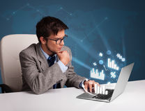 Young man sitting at desk and typing on laptop with diagrams and Stock Image