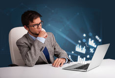 Young man sitting at desk and typing on laptop Royalty Free Stock Image