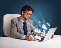 Young man sitting at desk and typing on laptop with diagrams and Stock Photo