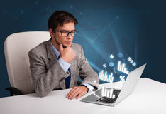 Young man sitting at desk and typing on laptop with diagrams and Royalty Free Stock Images