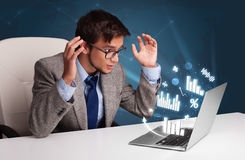 Young man sitting at desk and typing on laptop with diagrams and Royalty Free Stock Photo