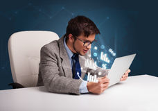 Young man sitting at desk and typing on laptop with diagrams and Royalty Free Stock Photos