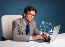 Young man sitting at desk and typing on laptop with social network icons. Attractive young man sitting at desk and typing on laptop with social network icons royalty free stock photos