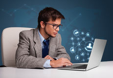 Young man sitting at desk and typing on laptop with social netwo Stock Image