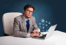 Young man sitting at desk and typing on laptop with social netwo Stock Images
