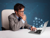 Young man sitting at desk and typing on laptop with social netwo Stock Photography