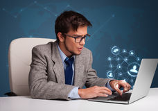 Young man sitting at desk and typing on laptop with social network icons. Attractive young man sitting at desk and typing on laptop with social network icons stock images
