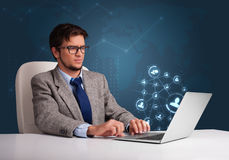 Young man sitting at desk and typing on laptop with social netwo Royalty Free Stock Photos