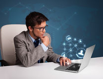 Young man sitting at desk and typing on laptop with social netwo Royalty Free Stock Photography