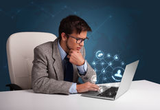 Young man sitting at desk and typing on laptop with social netwo Royalty Free Stock Image
