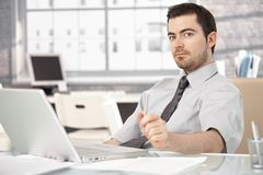 Young man sitting at desk using laptop Royalty Free Stock Image