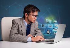 Young man sitting at desk and watching his photo gallery on lapt Stock Images