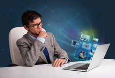 Young man sitting at desk and watching his photo gallery on lapt Royalty Free Stock Images