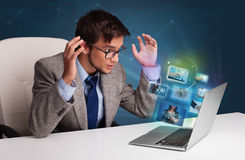 Young man sitting at desk and watching his photo gallery on lapt Stock Photos