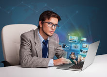 Young man sitting at desk and watching his photo gallery on lapt Royalty Free Stock Photo