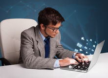 Young man sitting at dest and typing on laptop with message icon Stock Photo