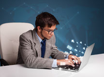 Young man sitting at dest and typing on laptop with message icon Royalty Free Stock Photography