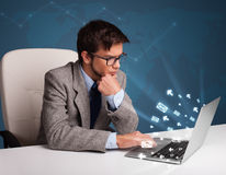 Young man sitting at dest and typing on laptop with message icon Stock Photos