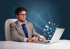Young man sitting at dest and typing on laptop with message icon Stock Image