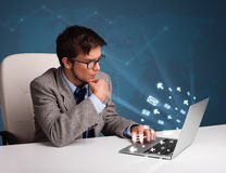 Young man sitting at dest and typing on laptop with message icon Royalty Free Stock Photo